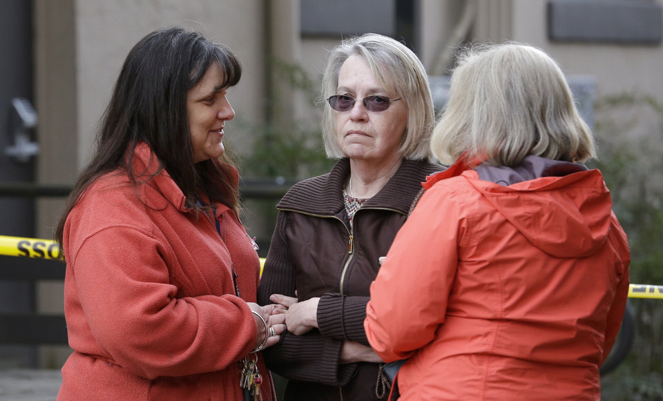 Photo - Barbara Welsh, center, whose husband is missing in a deadly mudslide, stands with relatives Monday, March 24, 2014, in Arlington, Wash.  The search for survivors of the deadly mudslide grew Monday to include 108 names of people who were reported missing or were unaccounted for, but authorities cautioned the figure would likely decline dramatically. The size of the list raised concerns the death toll would rise far above the eight people who have been confirmed dead after the 1-square-mile (2.6-square-kilometer) slide Saturday swept through part of a former fishing village about 55 miles (80 miles) northeast of Seattle. Several people also were critically injured. About 30 homes were destroyed, and the debris blocked a 1-mile (1.6 kilometer) stretch of state highway.   (AP Photo/Elaine Thompson)