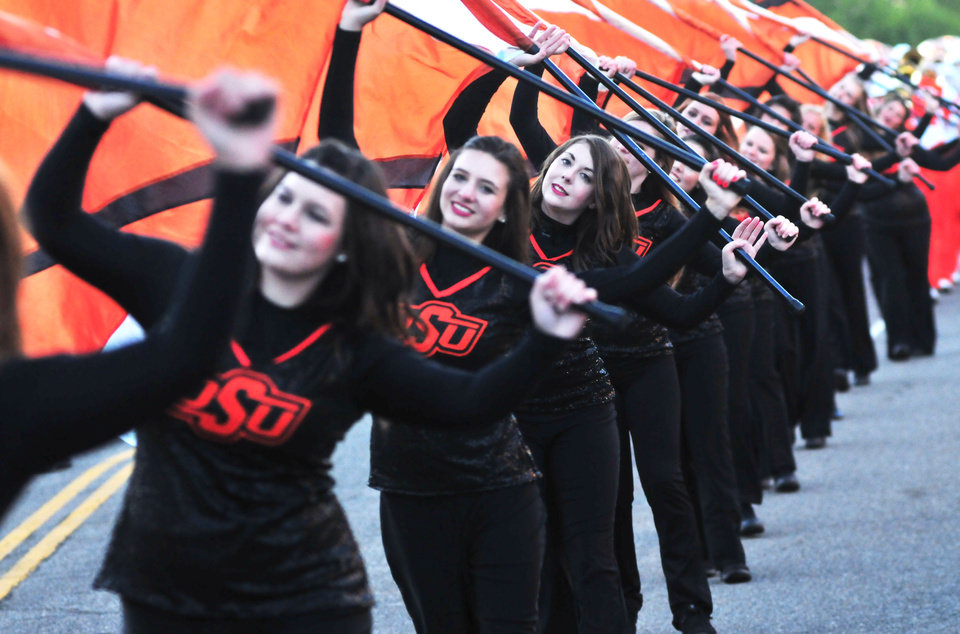 The Oklahoma State band flag girls walk in downtown Stillwater during the Sea of Orange Parade on October 19, 2013. Photo by KT King/For the Oklahoman