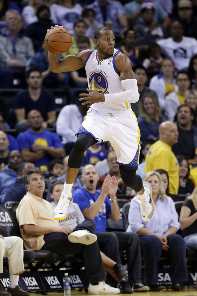Photo - Golden State Warriors' Andre Iguodala saves the ball from going out of bounds against the Sacramento Kings during the second half of an NBA preseason basketball game Monday, Oct. 7, 2013, in Oakland, Calif. (AP Photo/Marcio Jose Sanchez)