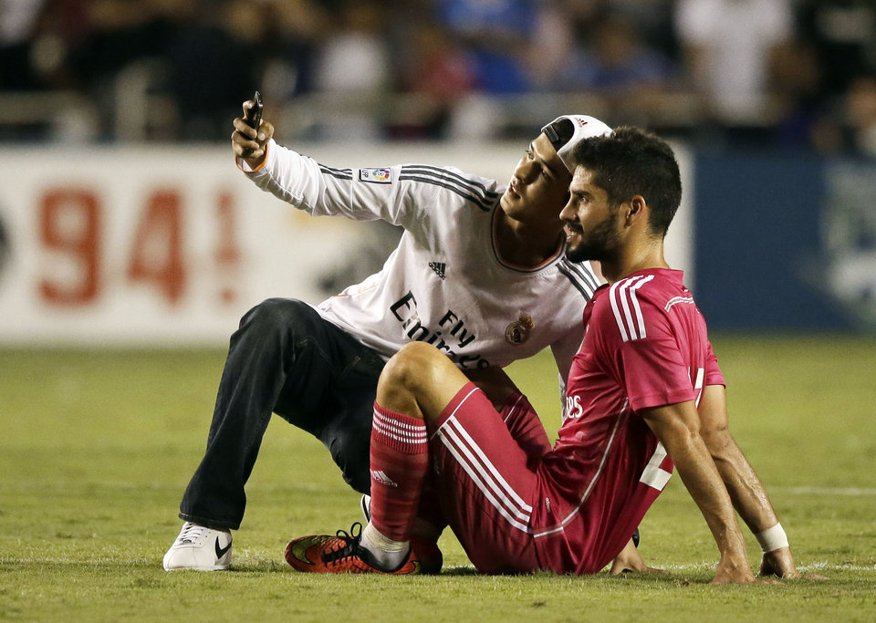 Photo - A fan that made it onto the field takes a selfie with Real Madrid's Isco, right, in the second half of a Guinness International Champions Cup soccer tournament match against Roma, Tuesday, July 29, 2014, in Dallas. Several fans made it onto the field, some able to acquire autographs from players, in the final minutes of the 1-0 Roma win. (AP Photo/Tony Gutierrez)