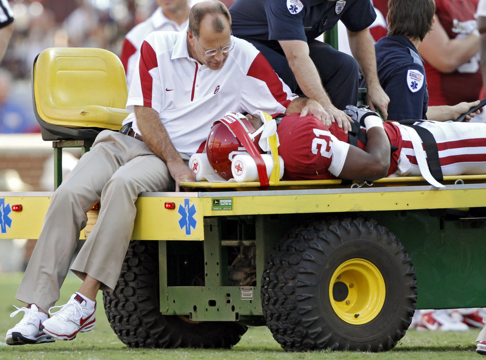 Photo - Trainers tend to Brennan Clay (21) after being injured on a play during the second half of the college football game between the University of Oklahoma Sooners (OU) and the Florida State University Seminoles (FSU) on Sat., Sept. 11, 2010, in Norman, Okla.  Photo by Chris Landsberger, The Oklahoman