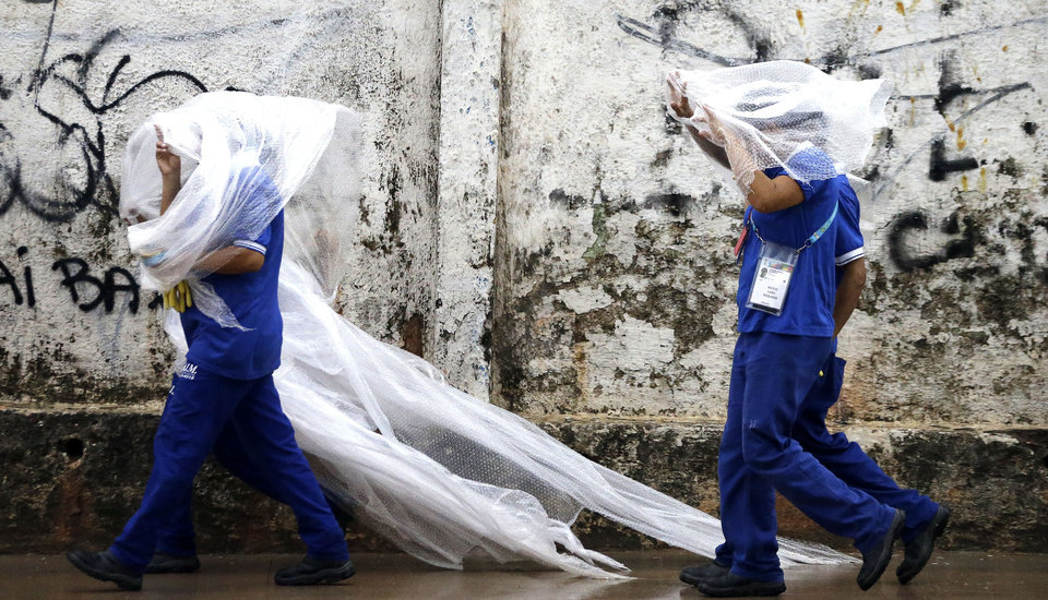 Photo - Workers cover themselves from the rain with a plastic as they leave a 2014 soccer World Cup venue, the Arena da Amazonia in Manaus, Brazil, Wednesday, June 11, 2014. The 2014 World Cup is set to begin Thursday, with Brazil and Croatia competing in the opening match in Sao Paulo. (AP Photo/Themba Hadebe)