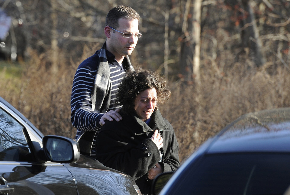 Photo - A man and woman leave the staging area for family around near the scene of a shooting at Sandy Hook Elementary School in Newtown, Conn. where authorities say a gunman opened fire, leaving 27 people dead, including 20 children, Friday, Dec. 14, 2012.  (AP Photo/Jessica Hill) ORG XMIT: CTJH108