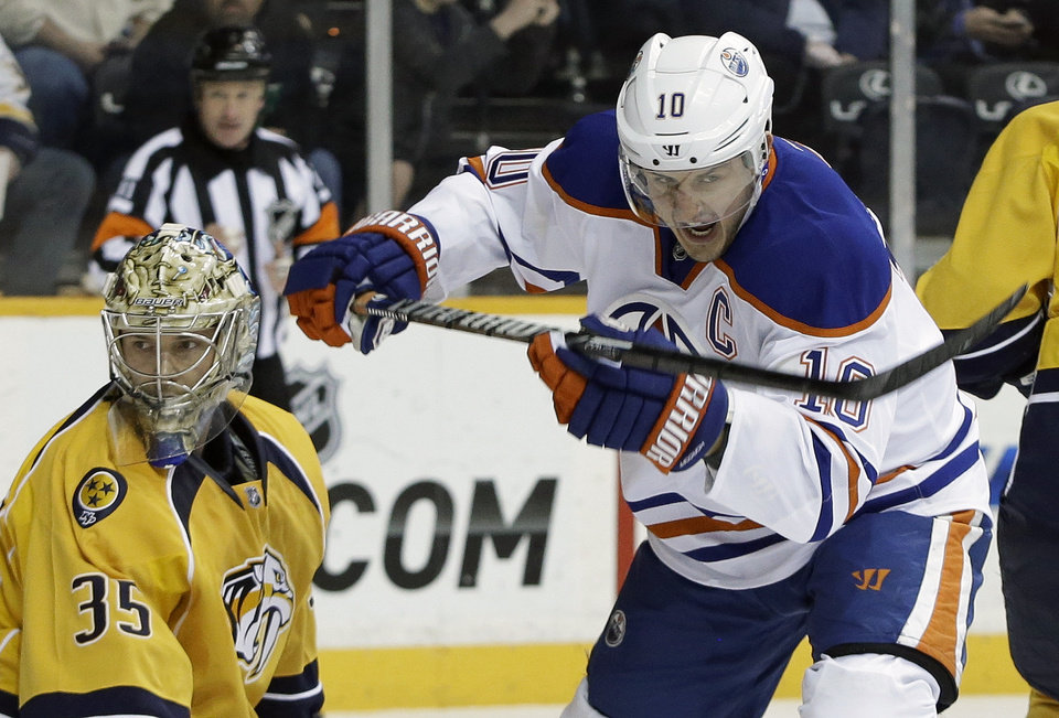 Photo - Edmonton Oilers center Shawn Horcoff (10) celebrates after a shot by teammate Corey Potter, unseen, got past Nashville Predators goalie Pekka Rinne (35), of Finland, for a goal in the first period of an NHL hockey game on Monday, March 25, 2013, in Nashville, Tenn. (AP Photo/Mark Humphrey)
