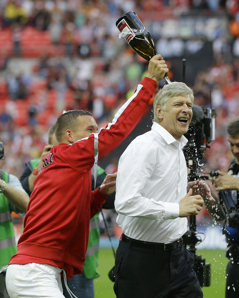 Photo - Arsenal's coach Arsene Wenger is doused with champagne by Lukas Podolski as they celebrate after winning the English FA Cup final soccer match between Arsenal and Hull City at Wembley Stadium in London, Saturday, May 17, 2014. Arsenal won 3-2 after extra-time. (AP Photo/Kirsty Wigglesworth)