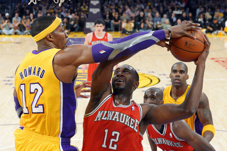 Los Angeles Lakers center Dwight Howard (12) blocks the shot of Milwaukee Bucks forward Luc Richard Mbah a Moute, of Cameroon, during the first half of their NBA basketball game, Tuesday, Jan. 15, 2013, in Los Angeles. (AP Photo/Mark J. Terrill)