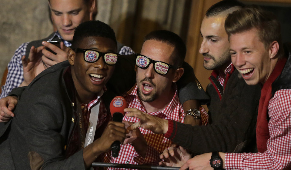 Photo - Bayern's David Alaba of Austria, from left, Franck Ribery of France, Diego Contento and Mitchell Weiser celebrate on the town hall balcony after winning the German Soccer Championship after the season's last home game between FC Bayern Munich and VfB Stuttgart, in Munich, southern Germany, Saturday, May 10, 2014. (AP Photo/Matthias Schrader)