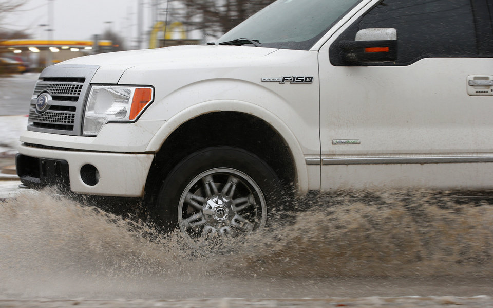 Photo - A truck splashes through slush as it moves along NW 150th in Oklahoma City, Sunday, December 27, 2015. Photo by Bryan Terry, The Oklahoman