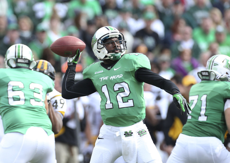 Photo - FILe - In this Nov. 2, 2013, file photo, Marshall quarterback Rakeem Cato passes during an NCAA college football game against Southern Mississippi in Huntington, W.Va. Cato enters his senior season with the chance to become the most prolific quarterback in school history. (AP Photo/The Herald-Dispatch, Marcus Constantino, File)