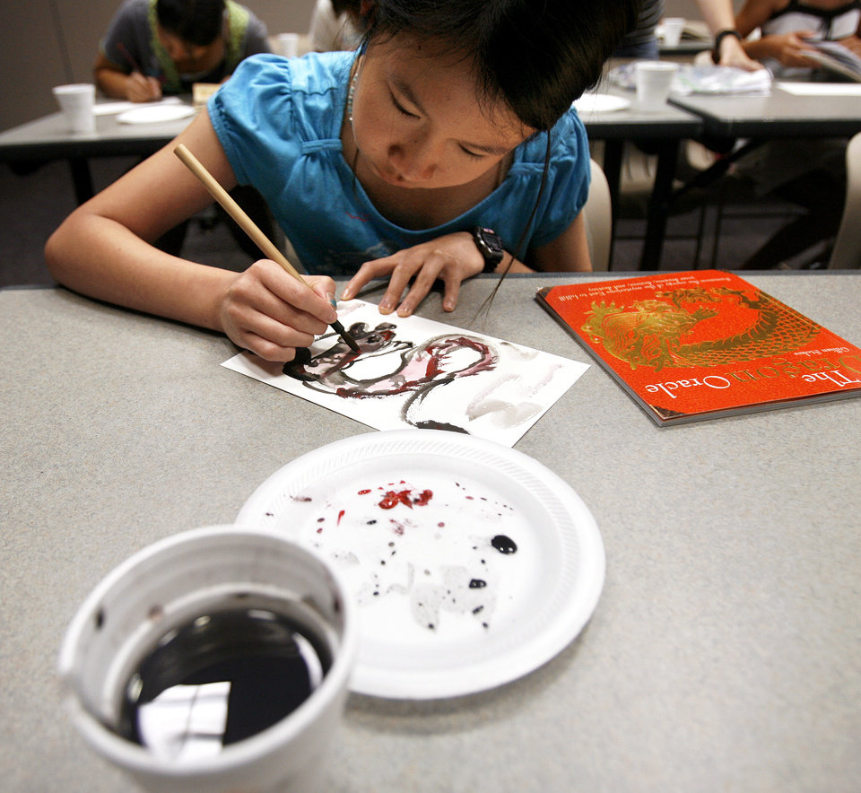Photo - Christinen Luk, 13, paints a dragon during a Chinese brush painting class at Edmond Public Library. PHOTOS BY ASHLEY MCKEE, THE OKLAHOMAN