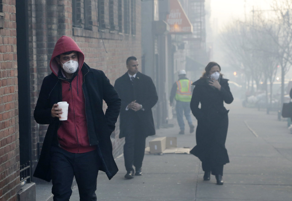 Photo - People wear dust masks as they walk near the site of a building explosion, Thursday, March 13, 2014 in New York.  Rescuers working amid gusty winds, cold temperatures and billowing smoke pulled four additional bodies Thursday from the rubble of two New York City apartment buildings, raising the death toll to at least seven from a gas leak-triggered explosion that reduced the area to a pile of smashed bricks, splinters and mangled metal.  The explosion Wednesday morning in Manhattan's East Harlem injured more than 60 people. (AP Photo/Mark Lennihan)