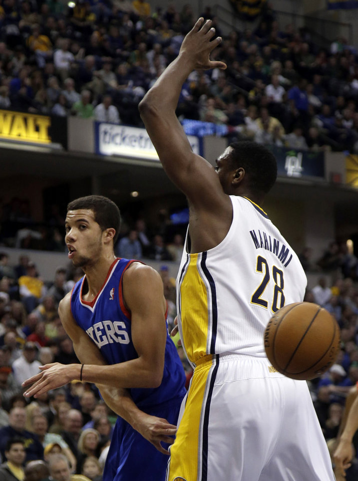 Photo - Philadelphia 76ers guard Michael Carter-Williams, left, makes a no look pass around Indiana Pacers center Ian Mahinmi (28) during the first half of an NBA basketball game in Indianapolis, Monday, March 17, 2014. (AP Photo/AJ Mast)