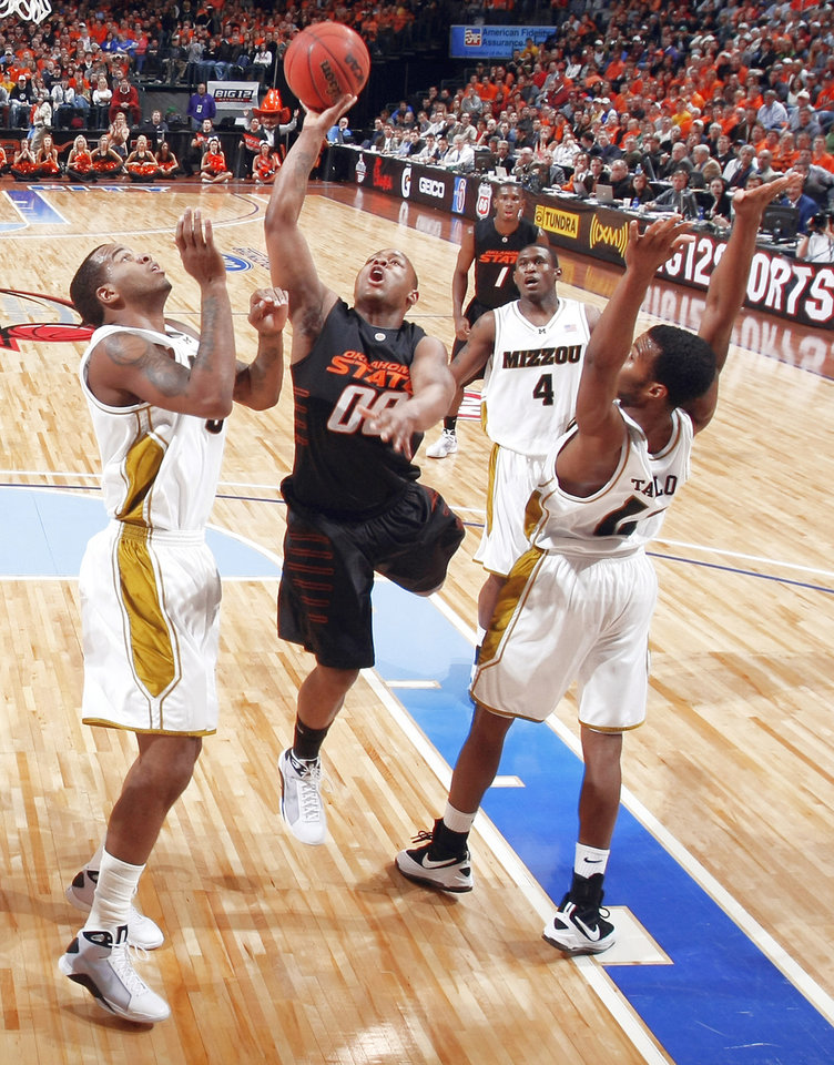 Photo - OSU's Byron Eaton, center, puts up a shot between Missouri's Leo Lyons, left, and Zaire Taylor on Friday. Photo by chris landsberger, the oklahoman
