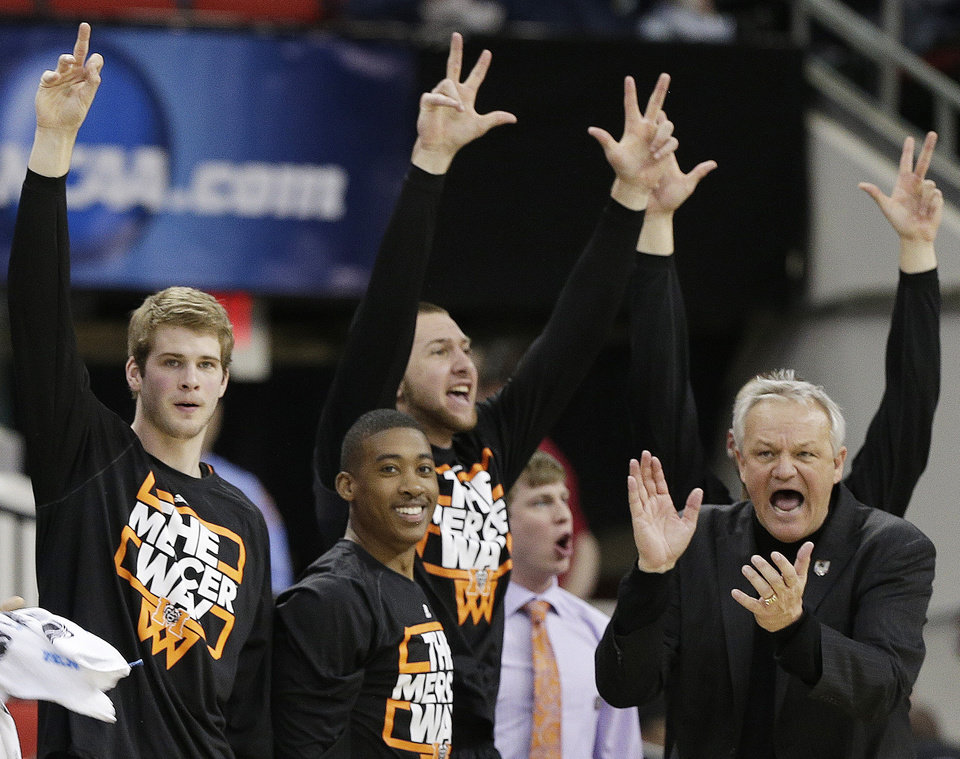 Photo - Mercer head coach Bob Hoffman and players react to a Mercer three-point shot during the second half of an NCAA college basketball second-round game against Duke, Friday, March 21, 2014, in Raleigh, N.C. (AP Photo/Chuck Burton)