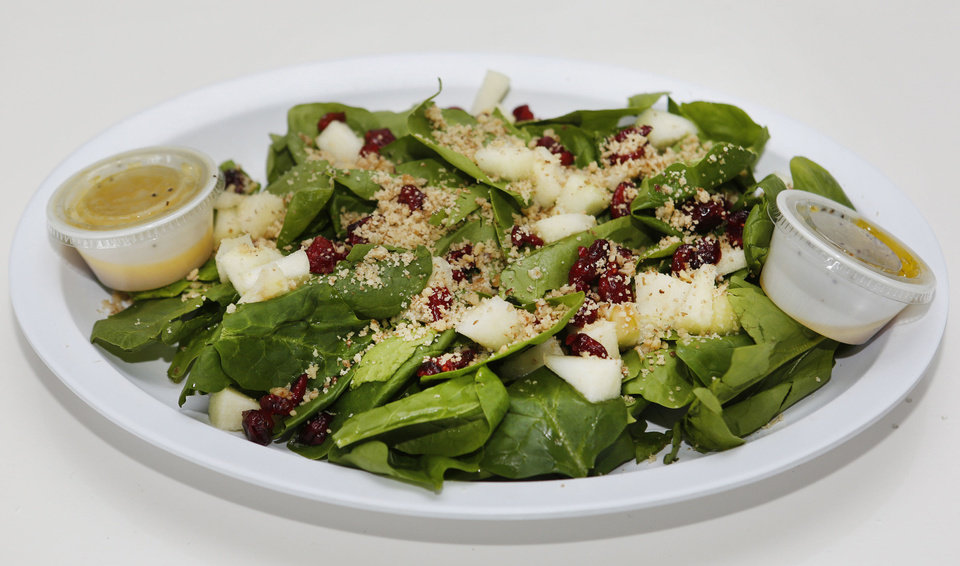 Photo - Apple Spinach Salad at Green and Grilled contains spinach, diced green apples, dried cranberries, chopped walnuts and house-made light orange vinaigrette.  Steve Gooch - The Oklahoman