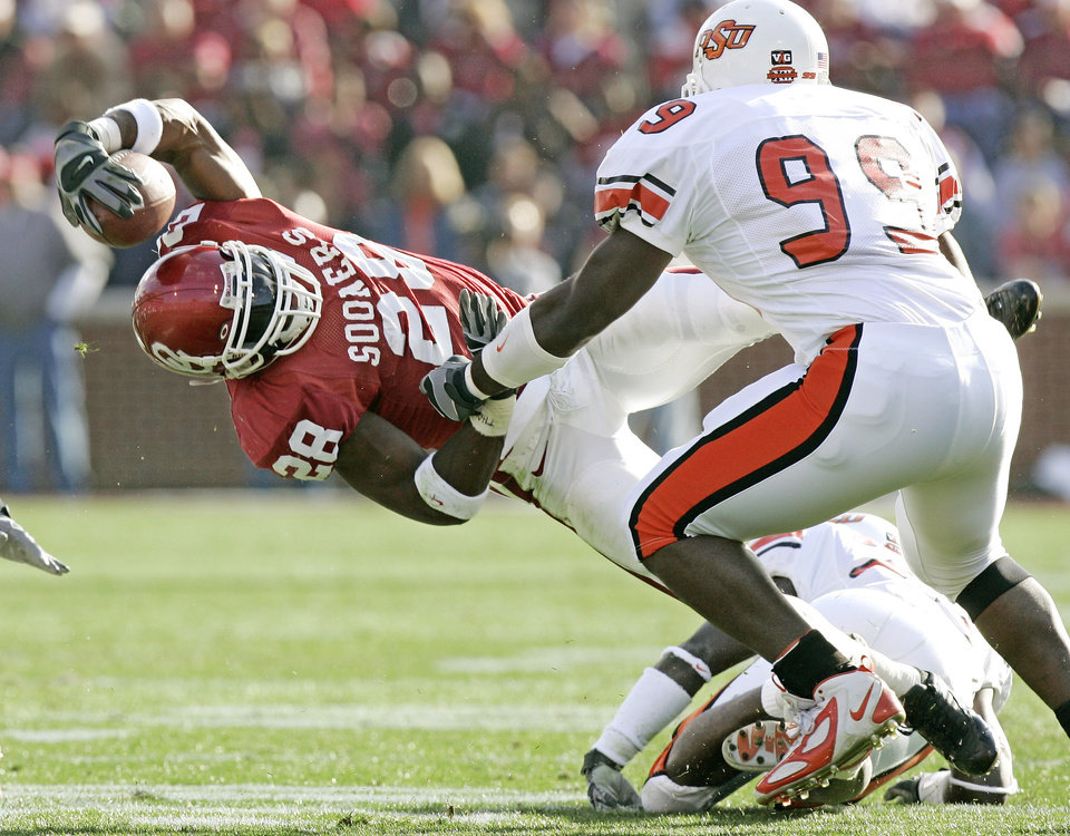 OU running back Adrian Peterson dives for yards after contact by OSU's Jamie Thompson (23 on ground) and Lawrence Pinson (99)  during the University of Oklahoma college football game against Oklahoma State University  at The Gaylord Family - Oklahoma Memorial Stadium, Saturday, November 26, 2005 in Norman, Oklahoma. This is the 100th Bedlam football game. By Doug Hoke /The Oklahoman