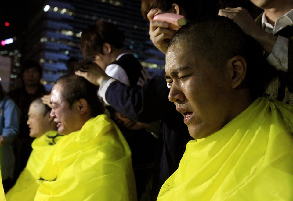Photo - College students have their heads shaved during a rally to call for thorough investigations into the sunken ferry Sewol in Seoul, South Korea, Thursday, May 15, 2014. Prosecutors indicted the captain of the sunken South Korean ferry and three crew members on homicide charges Thursday, alleging that they failed to carry out their duties to protect passengers in need.  (AP Photo/Ahn Young-joon)