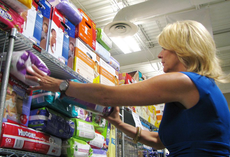 Photo - Miki Farris, executive director of Infant Crisis Services, looking through donated diapers at the nonprofit's headquarters off Lincoln north of the state Capitol.  VALLERY BROWN - STAFF WRITER