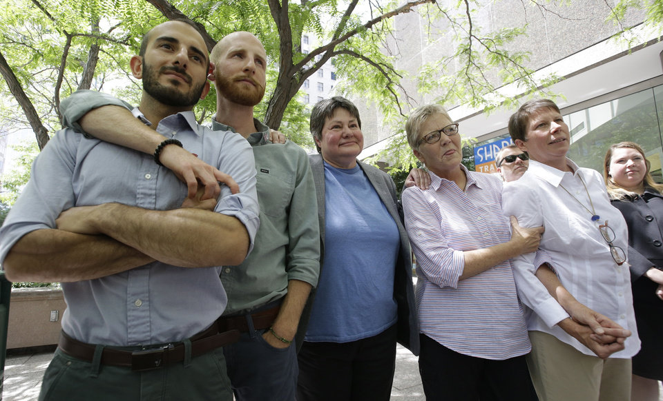 Photo - From left, plaintiffs Moudi Sbeity and Derek Kitchen, Kate Call, Laurie Wood and Kody Partridge, five of the six people who brought the lawsuit against the Utah's gay marriage ban, stand together at a news conference outside their lawyers office Wednesday, June 25, 2014, in Salt Lake City. Call's partner, Karen Archer, was not able to attend. On Wednesday, June 25, 2014, a federal appeals court in Denver ruled that states must allow gay couples to marry, finding the Constitution protects same-sex relationships. The decision from a three-judge panel in Denver upheld a lower court ruling that struck down Utah's gay marriage ban. (AP Photo/Rick Bowmer)