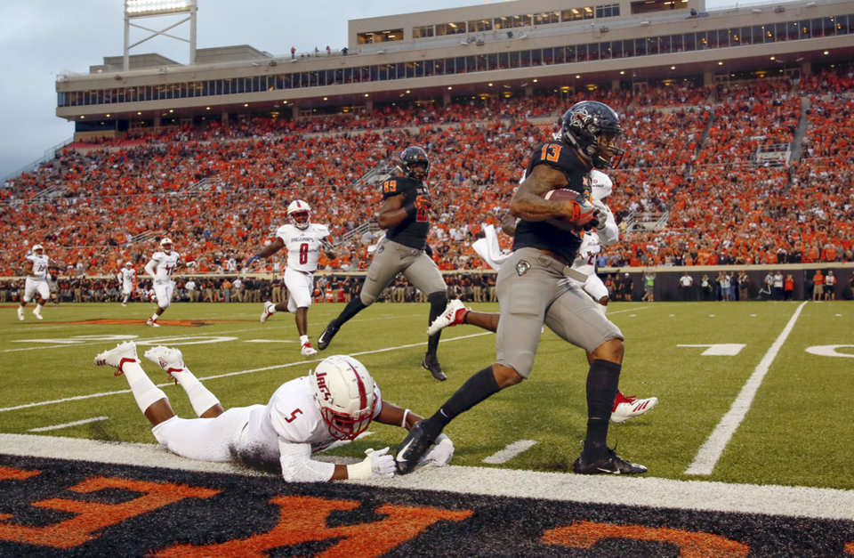 Photo - Oklahoma State's Tyron Johnson (13) goes out of bounds in front of South Alabama's Malcolm Buggs (5) after a long catch in the first quarter during a college football game between Oklahoma State (OSU) and South Alabama at Boone Pickens Stadium in Stillwater, Okla., Saturday, Sept. 8, 2018. Photo by Nate Billings, The Oklahoman