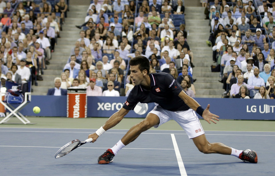 Photo - Novak Djokovic, of Serbia, returns a shot to Andy Murray, of Britain, during the quarterfinals of the U.S. Open tennis tournament Wednesday, Sept. 3, 2014, in New York. (AP Photo/Darron Cummings)