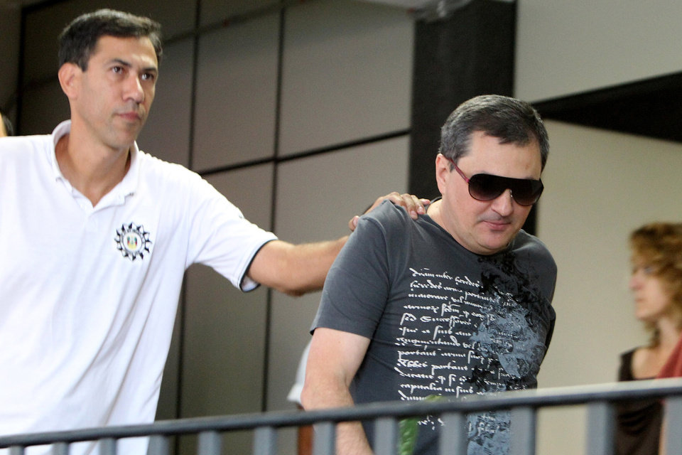 Photo - Mauro Hoffmann, right, co-owner of the Kiss nightclub, is escorted by police as he voluntarily surrenders at a police station in Santa Maria, Brazil, Monday, Jan. 28, 2013. A fast-moving fire roared through the crowded, windowless Kiss nightclub in this southern Brazilian city early Sunday, killing more than 230 people.  Brazilian police said they detained three other people in connection with the blaze. (AP Photo/Nabor Goulart)