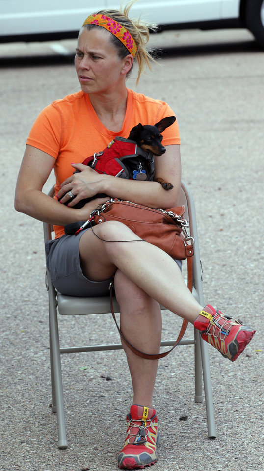 Photo - Dee Threet holds her dog Jim as she waits to talk to her insurance agent in Colorado Springs, Colo., on Thursday, June 13, 2013. Threet was evacuated from her home because of the Black Forest wildfire that has burned more than 350 homes since Tuesday. She doesn't know if her home burned. (AP Photo/Ed Andrieski)