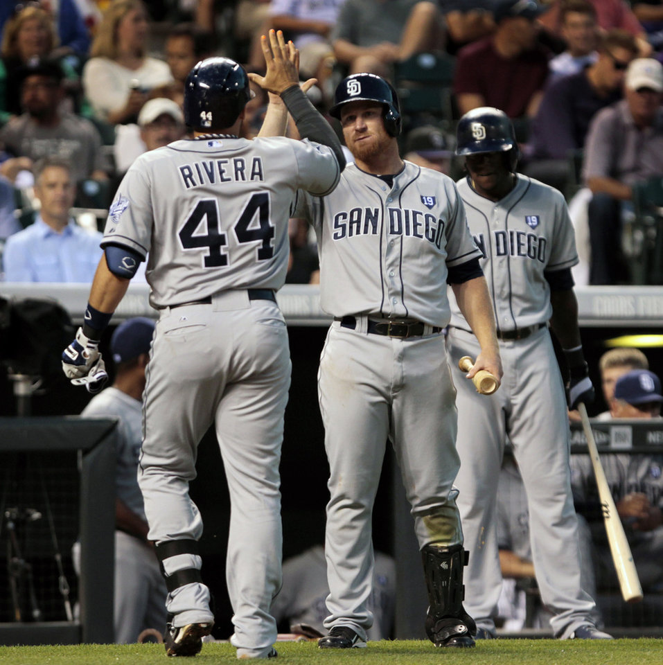 Photo - San Diego Padres' Rene Rivera (44) is congratulated by Padres' Brooks Conrad (11) after Rivera's solo home run in the sixth inning of a baseball game against the Colorado Rockies in Denver on Tuesday, July 8, 2014.(AP Photo/Joe Mahoney)