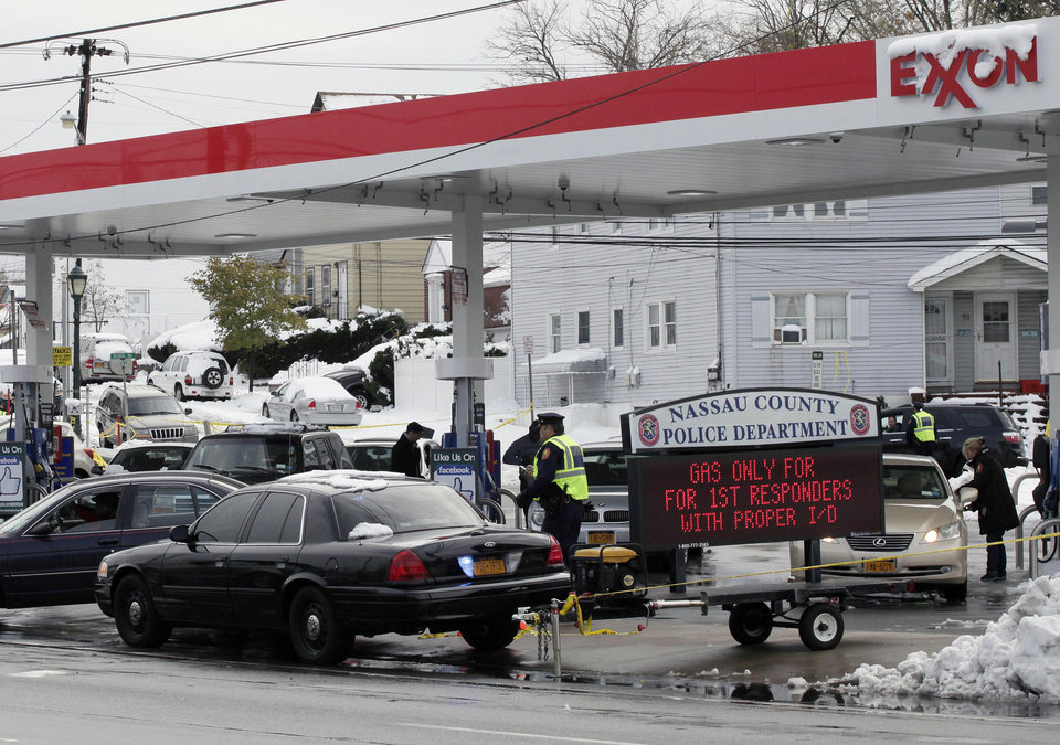 Nassau County Police control access to an Exxon station in Elmont, N.Y., Thursday, Nov. 8, 2012. Gasoline supplies have been limited in the region since Superstorm Sandy hit ten days ago. The police are limiting sales of gasoline at this Long Island station to first responders. (AP Photo/Mark Lennihan)