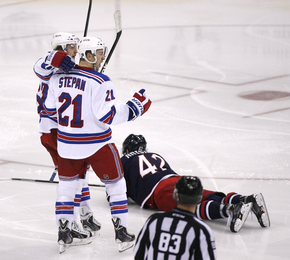 Photo - New York Rangers' Derek Stepan (21) celebrates his goal during the third period of an NHL hockey game, Friday, March 21, 2014, in Columbus, Ohio. Columbus Blue Jackets' Artem Anisimov (42), of Russia, is on the ice. The Rangers won 3-1. (AP Photo/Mike Munden)