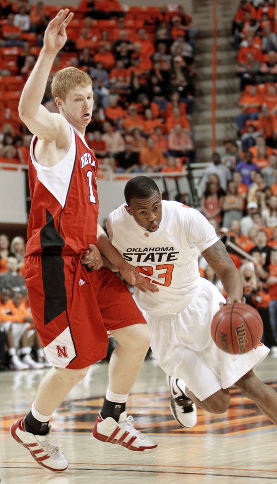 Photo - OSU's James Anderson, right, drives past Nebraska's Brandon Ubel .  Photo by Doug Hoke,  The Oklahoman
