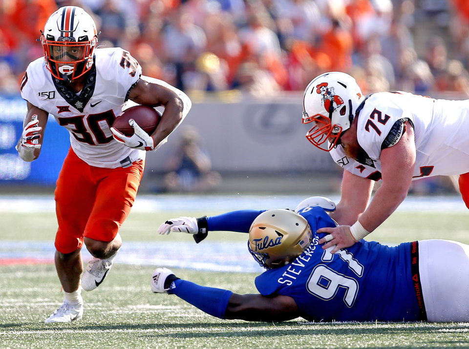 Photo - Oklahoma State's Chuba Hubbard (30) rushes as Johnny Wilson (72) blocks Tulsa's Tyarise Stevenson (97) during a college football game between the Oklahoma State University Cowboys (OSU) and the University of Tulsa Golden Hurricane (TU) at H.A. Chapman Stadium in Tulsa, Okla., Saturday, Sept. 14, 2019. [Sarah Phipps/The Oklahoman]