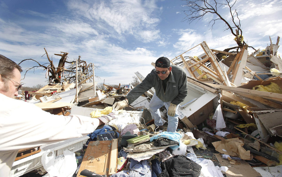 Jimmy Wyatt, right, hands items to Lynn Self to clean up tornado damage, Thursday, Feb. 12, 2009, in Lone Grove, Okla. The pair was helping clean debris from their friend\'s home who died in the tornado. PHOTO BY SARAH PHIPPS, THE OKLAHOMAN