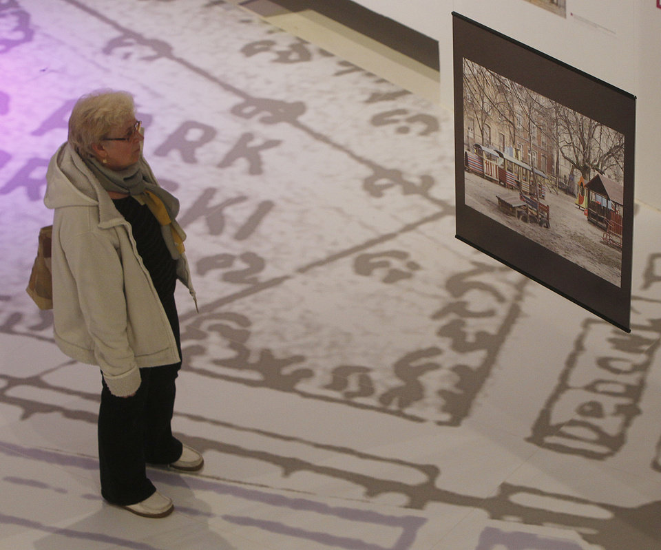 Photo - A visitor looks at an contemporary image of a site that used to be part of the Jewish district in pre-World War II Warsaw, at a new exhibition by the Museum of the History of Polish Jews, in Warsaw, Poland, on Thursday, March 27, 2014. The exhibition that will run through June 30 documents Jewish life in Warsaw before the Holocaust.(AP Photo/Czarek Sokolowski)