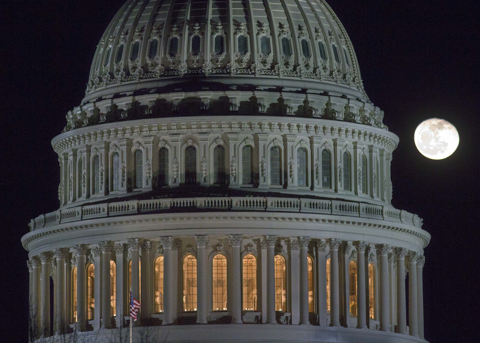 Photo - The moon rises behind the U.S. Capitol Dome in Washington as Congress works into the late evening, Sunday, Dec. 30, 2012 to resolve the stalemate over the pending
