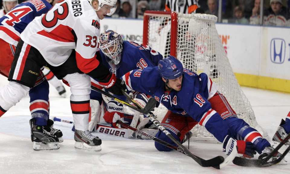 Photo -   New York Rangers' Marc Staal (18) tries to take control of the puck against Ottawa Senators' Jakob Silfverberg (33), of Sweden, during the third period of Game 7 of a first-round NHL hockey Stanley Cup playoff series on Thursday, April 26, 2012, in New York. The Rangers won 2-1. (AP Photo/Julio Cortez)