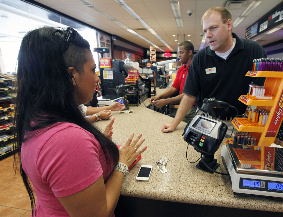 Photo - Giovannia Gonzalez purchases her first lottery tickets Friday from store manager David Schwarz at the OnCue store at N 23 and Santa Fe Avenue in Oklahoma City. Photo By Paul Hellstern, The Oklahoman  PAUL HELLSTERN