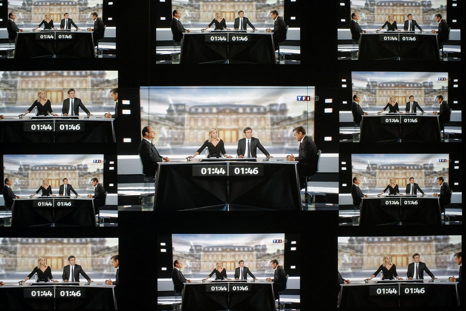 Photo -   A wall screen shows the televised debate between Socialist Party candidate for the presidential election Francois Hollande and current President and conservative rival for re-election, Nicolas Sarkozy, at the TF1 television studio, in Boulogne-Billancourt, outside Paris, Wednesday, May 2, 2012. The prime-time debate between conservative incumbent Sarkozy and his leftist challenger Hollande is billed in newspaper headlines Wednesday as