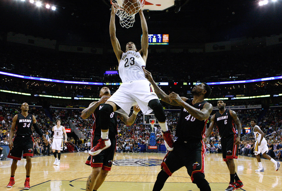 Photo - New Orleans Pelicans forward Anthony Davis (23) dunks the ball over Miami Heat defenders Udonis Haslem, right, and Michael Beasley, left, during the first half of an NBA basketball game in New Orleans, Saturday, March 22, 2014. (AP Photo/Jonathan Bachman)