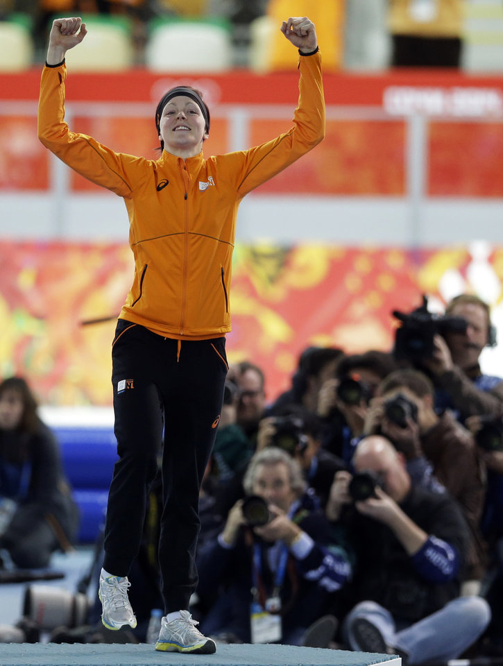 Photo - Photographers huddle together to shoot gold medallist Jorien ter Mors of the Netherlands as she jumps in celebration during the flower ceremony for the women's 1,500-meter speedskating race at the Adler Arena Skating Center during the 2014 Winter Olympics in Sochi, Russia, Sunday, Feb. 16, 2014. (AP Photo/Patrick Semansky)