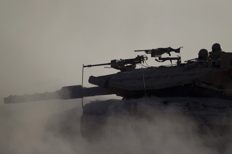 Photo - An Israeli tank takes a position along the Israel-Gaza Border, Thursday, July 17, 2014. Israel and Hamas have begun observing a five-hour humanitarian cease-fire, as fighting extended into a 10th day. The two sides agreed to the pause following a request by the United Nations so that supplies could be delivered to Gaza.(AP Photo/Ariel Schalit)