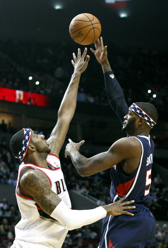 Atlanta Hawks forward Josh Smith, right, shoots over Portland Trail Blazers forward LaMarcus Aldridge during the first half of their NBA basketball game in Portland, Ore., Monday, Nov. 12, 2012. (AP Photo/Don Ryan)
