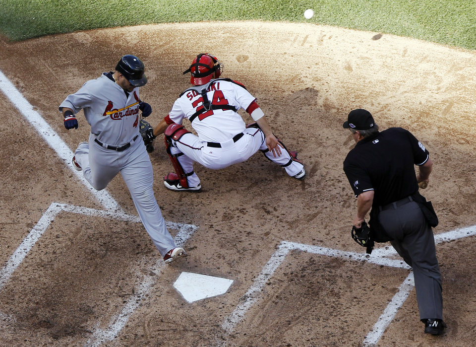 St. Louis Cardinals\' Yadier Molina, left, scores a run in front of Washington Nationals catcher Kurt Suzuki on a sacrifice fly by Daniel Descalso in the sixth inning of Game 3 of the National League division baseball series against the Washington Nationals on Wednesday, Oct. 10, 2012, in Washington. Home plate umpire Joe West, right, watches the play. (AP Photo/Alex Brandon)