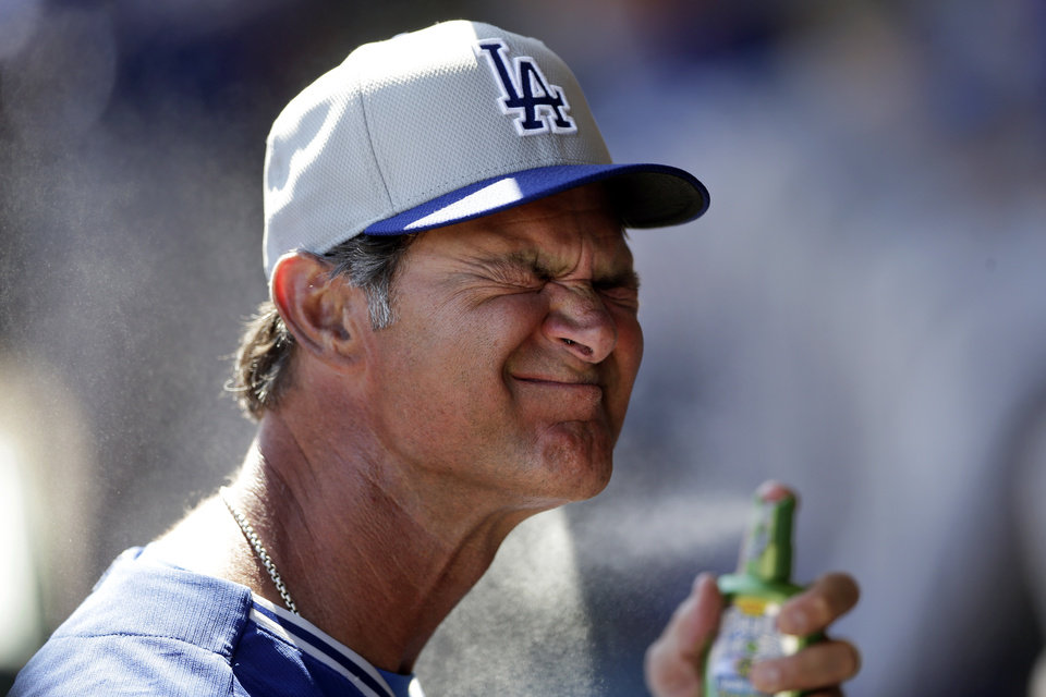 Photo - Los Angeles Dodgers manager Don Mattingly sprays on suntan lotion in the dugout before the Dodgers play the Oakland Athletics in a spring training baseball game Monday, March 3, 2014, in Phoenix. (AP Photo/Gregory Bull)