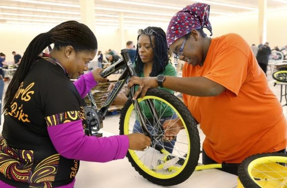 Photo -  Kimberly Mackall, left, Cyndi Mundine and Janetta Rooks, members of Black Girls Do Bike Oklahoma, volunteer as bicycle assemblers at the 2018