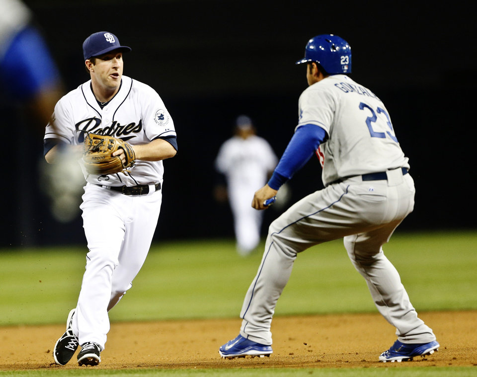 Photo - San Diego Padres second baseman Jedd Gyorko chases down Los Angeles Dodgers' Adrian Gonzalez while executing  a double play to end the first innning of an MLB National League baseball game Wednesday, April 2, 2014, in San Diego.  (AP Photo/Lenny Ignelzi)