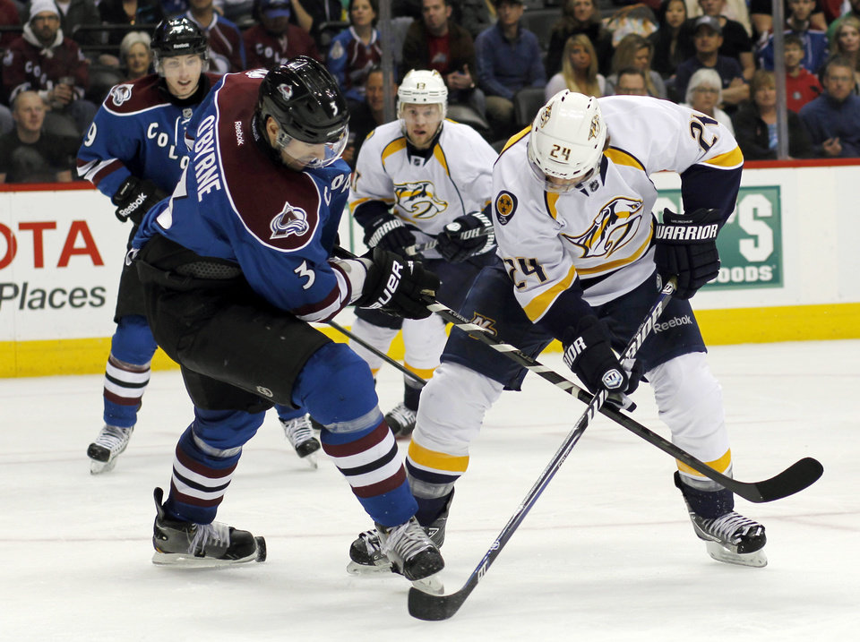 Photo - Colorado Avalanche defenseman Ryan O'Byrne, left, gets tangled up as he blocks a shot off the stick of Nashville Predators right wing Matt Halischuk in the second period of an NHL hockey game in Denver on Saturday, March 30, 2013. (AP Photo/David Zalubowski)