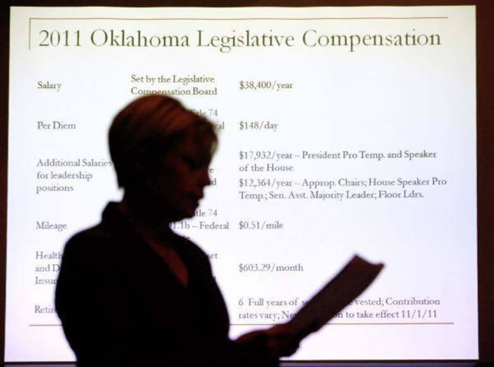 Photo - Shelly Paulk, revenue analyst for the Office of State Finance, is silhouetted in front of a screen a showing legislative salaries while speaking during a meeting of the Legislative Compensation Board at the state Capitol in Oklahoma City Tuesday, Oct. 18, 2011. Photo by Paul B. Southerland, The Oklahoman ORG XMIT: KOD