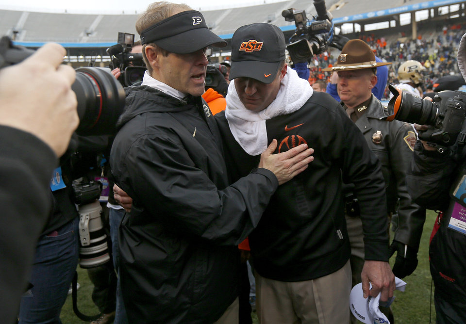 Photo - Oklahoma State coach Mike Gundy meets with Purdue interim coach Patrick Higgins after the Heart of Dallas Bowl football game between Oklahoma State University and Purdue University at the Cotton Bowl in Dallas, Tuesday, Jan. 1, 2013. Oklahoma State won 58-14. Photo by Bryan Terry, The Oklahoman