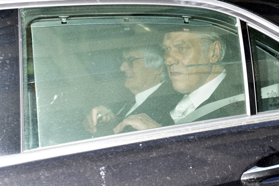 Photo - Bernie Ecclestone, left, the 83-year-old controlling business magnate in Formula One racing, sits in a car on his way to the regional court in Munich , Germany, Thurstay, April 24, 2014. Ecclestone is charged with bribery and incitement to breach of trust